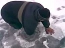 Russian man catches a big fish with bare hands from an ice hole