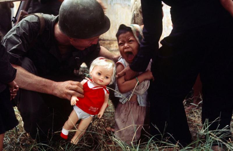 Американский морпех предлагает куклу ребёнку, Вьетнам, 1965 год.
