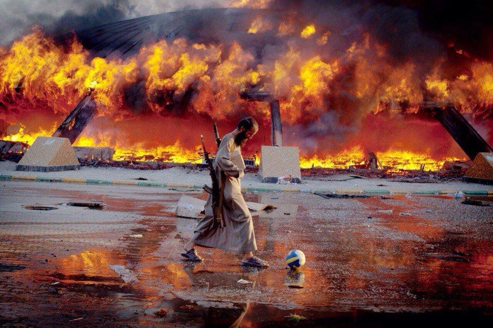 Мятежник играет в футбол на фоне пылающей резиденции М.Каддафи. Триполи, 2011 год