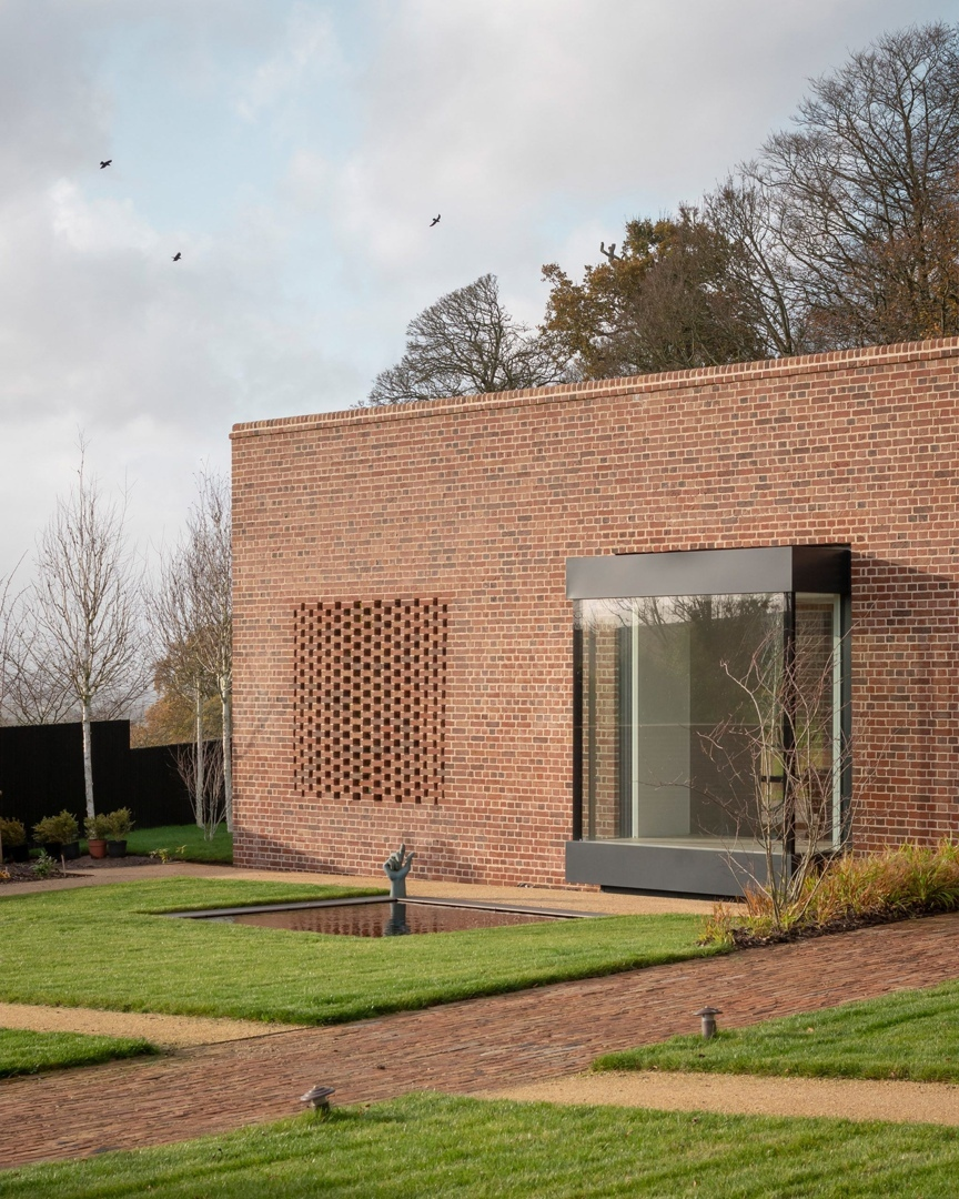 Linear brick wall conceals earthy and tactile interiors of Devon Passivhaus // 01