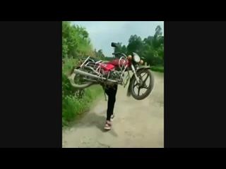 Девушка несёт на спине мотоцикл, байкерша поднимает мот в гору