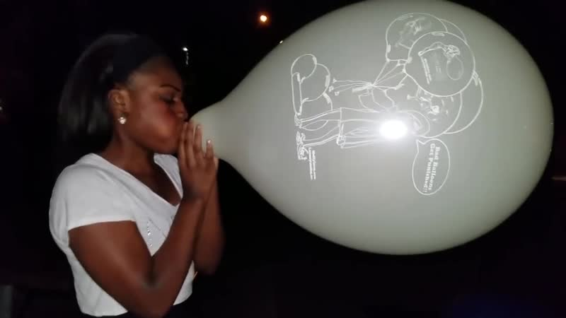 Girl blowing up an XXL balloon until it pops